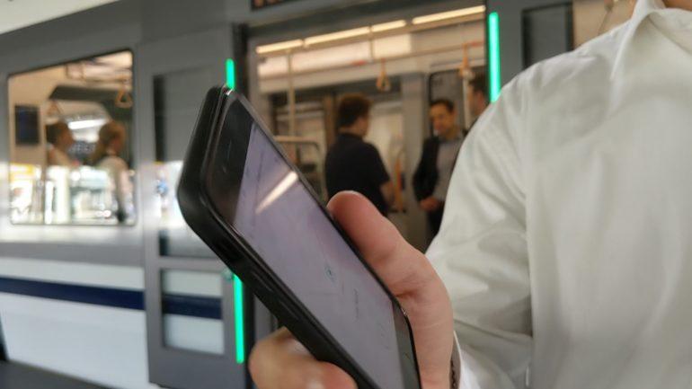Hand hält Smartphone vor einer Straße